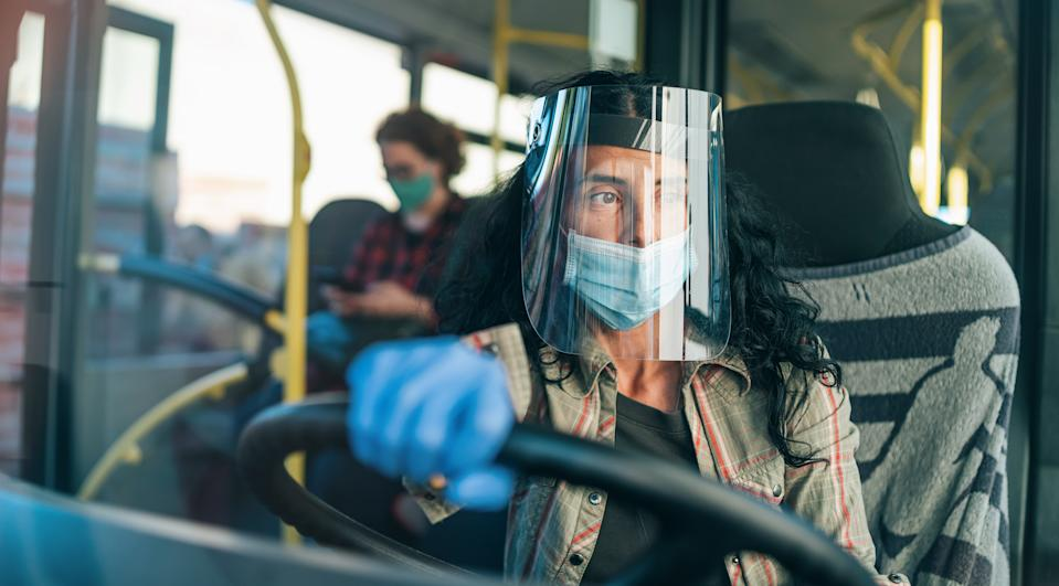 Female bus driver with protective mask working during COVID-19