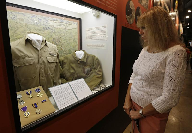 Karen Warner views a display on the Ploesti Raid in World War II that shows a shirt worn by her father, Lt. Col. Jack Warner, while touring the United States Air Force Museum, Wednesday, July 31, 2013, in Dayton, Ohio. The planes flew a dangerous low altitude raid on Aug. 1, 1943, targeting heavily defended oil fields in occupied Romania. Survivors of the raid are having a 70th reunion Thursday in Dayton. (AP Photo/Al Behrman)