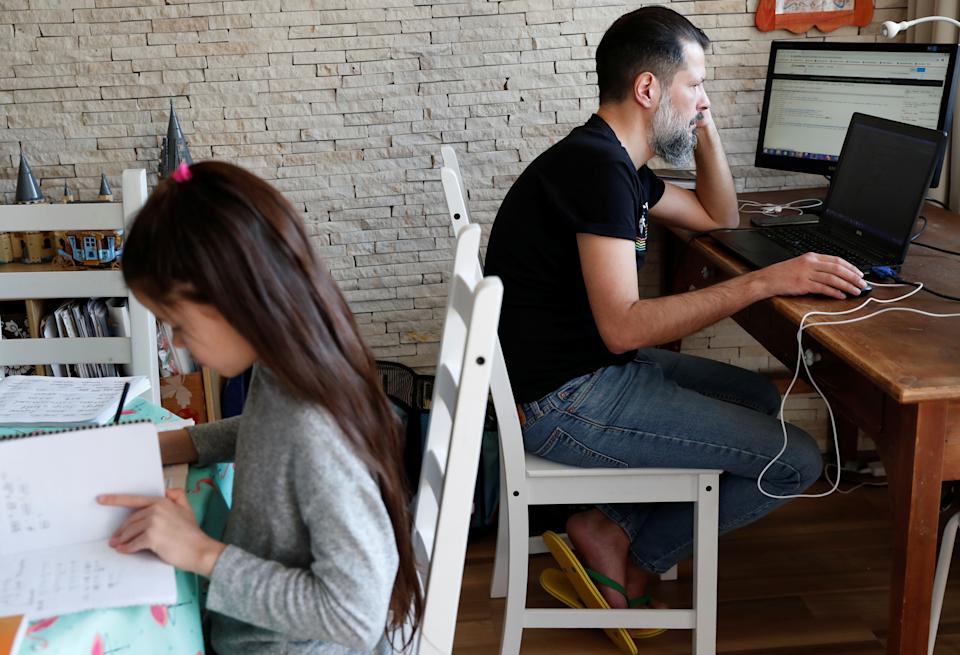 Csaba Posta, IT specialist working from home, studies with his daughter Vilma during the spread of coronavirus disease (COVID-19) in Budapest, Hungary March 19, 2020. REUTERS/Bernadett Szabo
