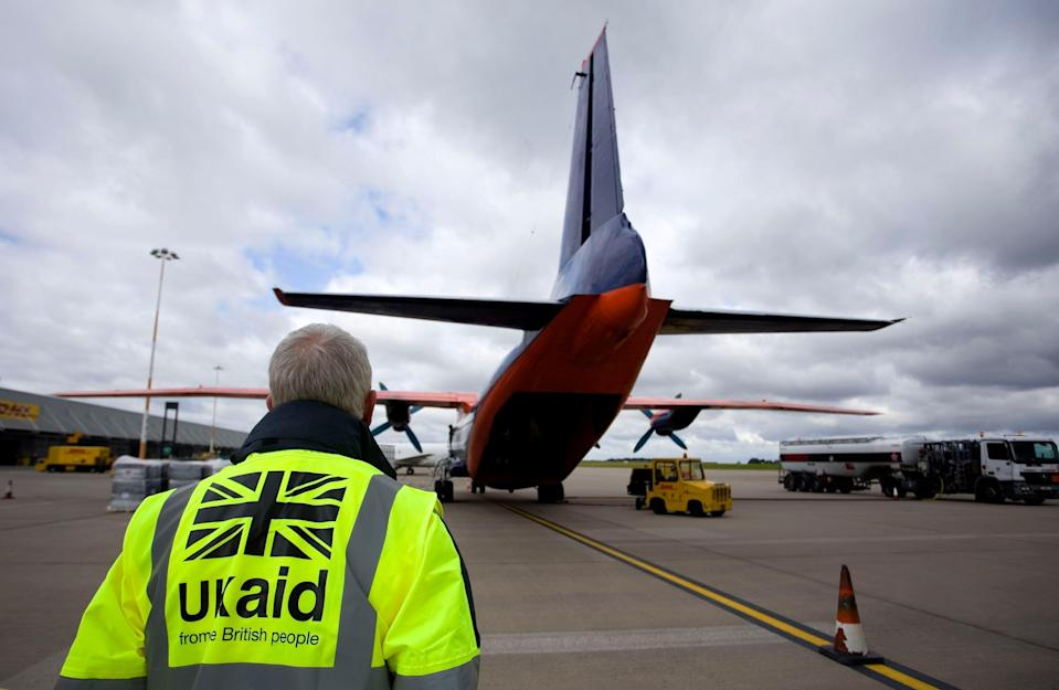 Staff from UK Aid watch as cargo is loaded on to a plane (PA Archive)