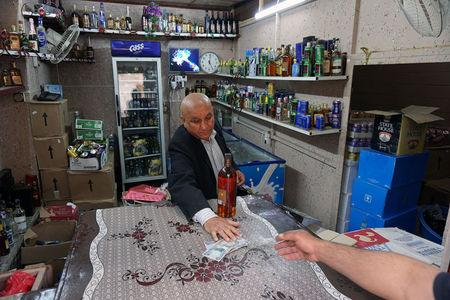 A man sells liquor in his shop in Mosul