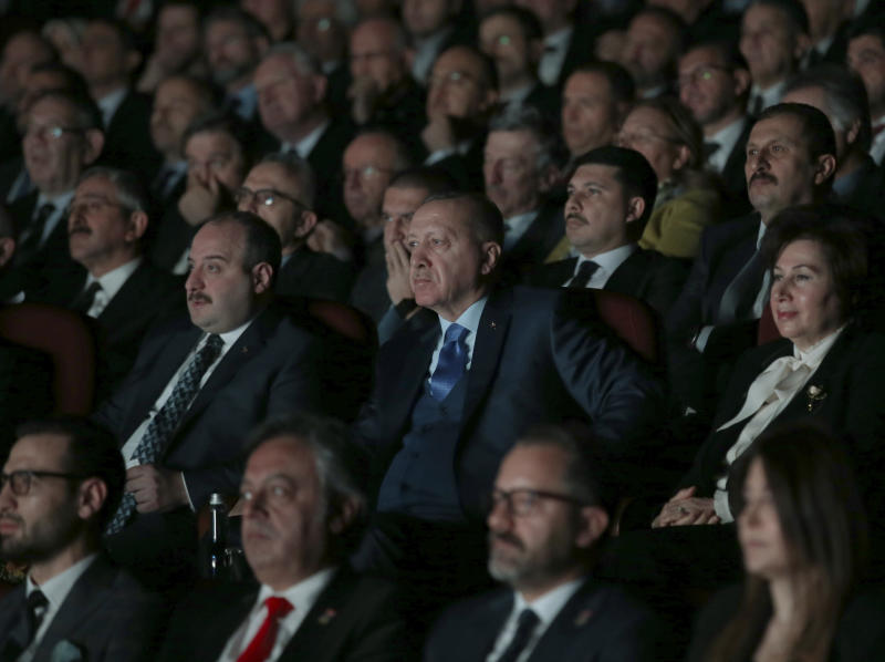 Turkey's President Recep Tayyip Erdogan centre, attends an event in Ankara, Turkey, Monday, Dec. 30, 2019. Turkey's government on Monday submitted a motion to parliament seeking approval to deploy troops to Libya, to help authorities in Tripoli defend the city from an offensive by rival forces, arguing that the conflict in the North African country could escalate into a civil war and threaten Turkey's interests.(Presidential Press Service via AP, Pool)
