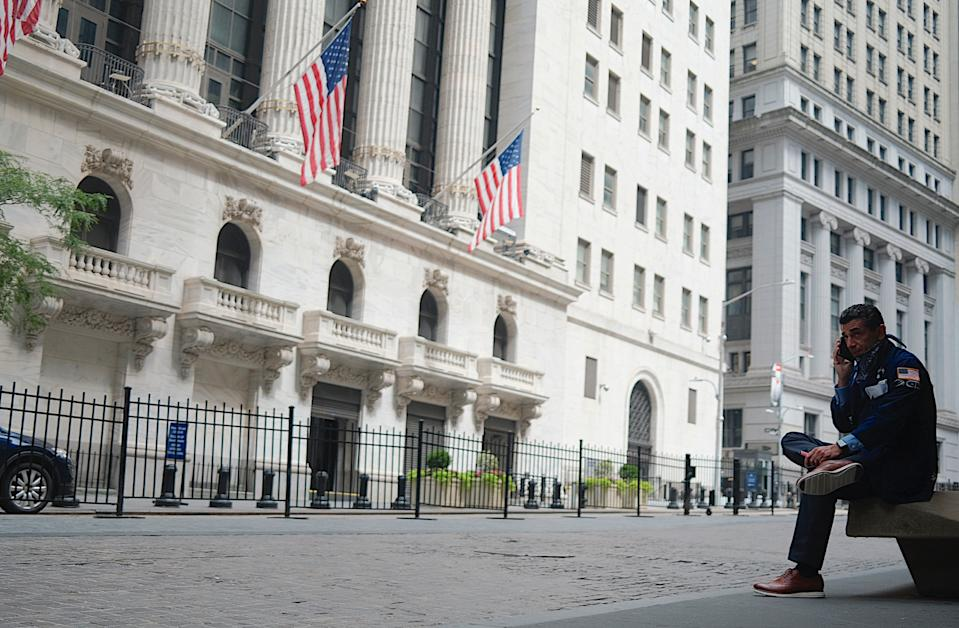 A trader makes a phone call outside the New York Stock Exchange (NYSE) on July 20, 2020 at Wall Street in New York City. - Wall Street stocks were mixed early July, 20, 2020 as markets awaited congressional debate on another round of stimulus spending and major earnings releases later in the week. (Photo by Johannes EISELE / AFP) (Photo by JOHANNES EISELE/AFP via Getty Images)