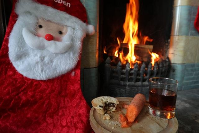 A mince pie, glass of sherry and a carrot for reindeers are left by a fireplace
