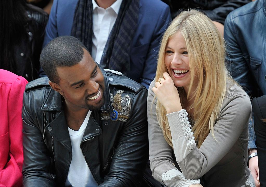 """Hip-hop star Kanye West and actress Sienna Miller have a love of fashion in common. The two sat together at the Burberry Spring Summer 2012 Womenswear Show at Kensington Gardens in London on Monday. And it looks like Kanye tells some good jokes! Gareth Cattermole/<a href=""""http://www.gettyimages.com/"""" target=""""new"""">GettyImages.com</a> - September 19, 2011"""