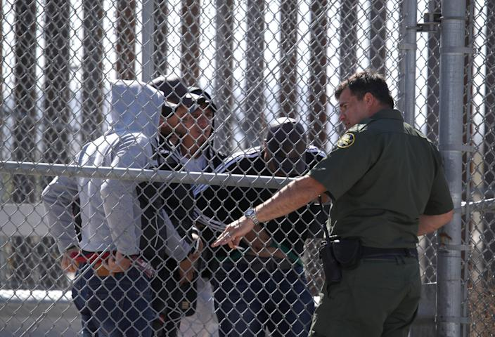 A U.S. Border Patrol agent talks with detained migrants at the border of the United States and Mexico on March 31, 2019 in El Paso, Texas. U.S. President Donald Trump has threatened to close the United States border if Mexico does not stem the flow of illegal migrants trying to cross. (Photo by Justin Sullivan/Getty Images)