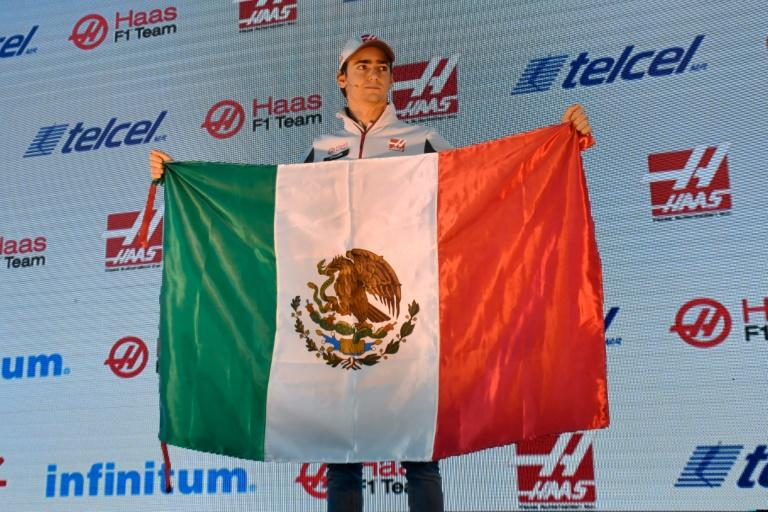 HAAS F1 Team's Mexican driver Esteban Gutierrez holds a Mexican national flag during press conference in Mexico City
