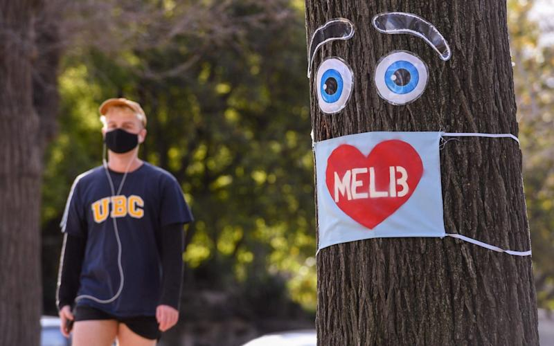 A man walks past a large face mask pinned to a tree in Melbourne today - WILLIAM WEST/AFP via Getty Images