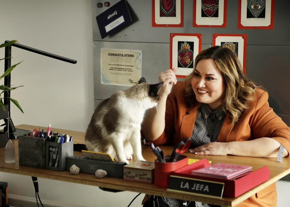 """Showrunner Tanya Saracho sits at her desk which has a sign that reads """"La Jefa"""" and plays with her cat"""