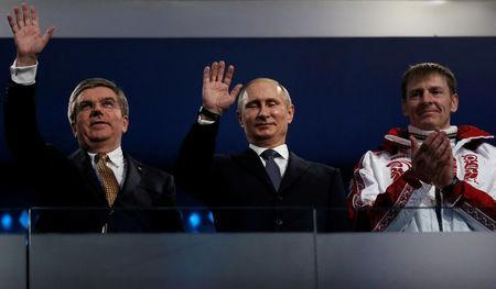 FILE PHOTO: International Olympic Committee (IOC) President Thomas Bach of Germany and Russian President Vladimir Putin wave as gold medallist bobsleigh athlete Russia's Alexander Zubkov applauds (L-R) during the closing ceremony for the 2014 Sochi Winter Olympics, February 23, 2014. REUTERS/Phil Noble/File Photo