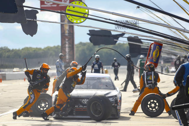 Crew members dash around the car of Martin Truex Jr. as they perform a pit stop during the NASCAR Cup Series auto race at Pocono Raceway, Saturday, June 27, 2020, in Long Pond, Pa. (AP Photo/Matt Slocum)