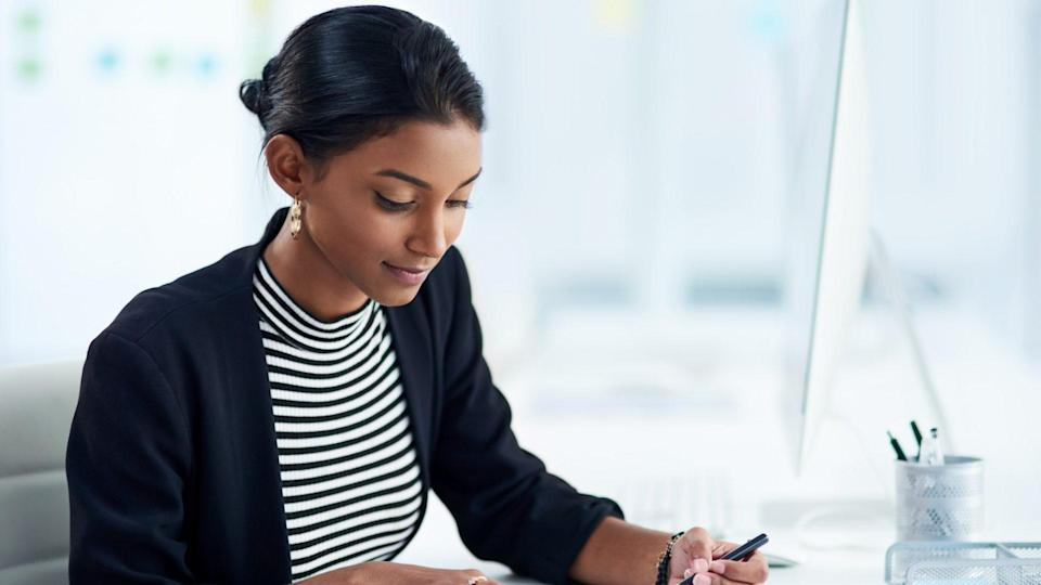 Shot of an attractive young businesswoman going over paperwork inside her office at work.