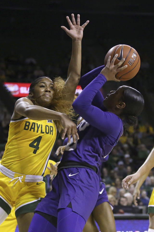 Baylor guard Te'a Cooper (4) tries to block the shot by TCU guard Lauren Heard (20) in the first half of an NCAA college basketball game, Wednesday, Feb. 12, 2020, in Waco, Texas. (AP Photo/Jerry Larson)