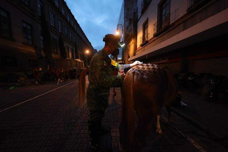 VARIOUS CITIES, MEXICO - SEPTEMBER 16: Mexican soilders prepare their horses during the Independence Day military parade at Zocalo Square on September 16, 2020 in Various Cities, Mexico. This year El Zocalo remains closed for general public due to coronavirus restrictions. Every September 16 Mexico celebrates the beginning of the revolution uprising of 1810. (Photo by Hector Vivas/Getty Images)