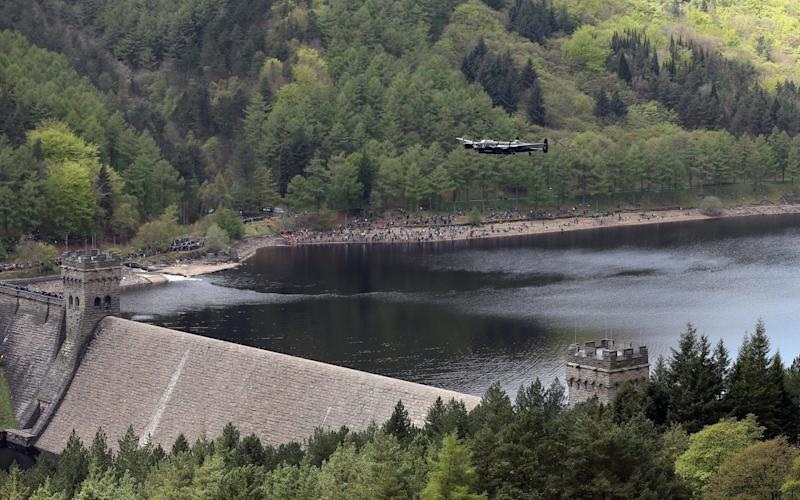 A Lancaster bomber flies over Ladybower reservoir in the Derbyshire Peak District to mark the 70th anniversary of the World War Two - Credit: Christopher Furlong/Getty Images