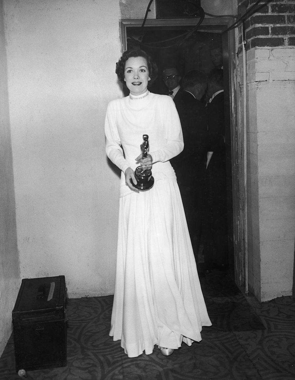 <p>The long-sleeve, high-collar dress was a popular silhouette back in the day, but Jane differentiated herself from the crowd with one in a bright-white color. She wore her pearl necklace over the fabric and clutched her Oscar award for her performance in <em>Johnny Belinda</em>.</p>