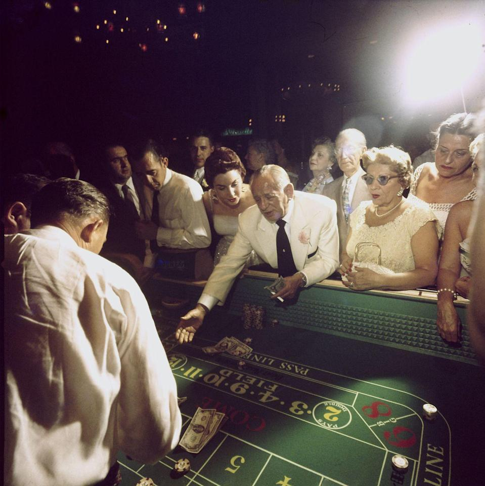 <p>Hotel owner Jake Freedman rolls dice at a craps table at the Dunes in 1955. The casino closed one year after Freedman bought it.</p>