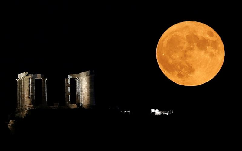 August's Sturgeon Moon rises behind the Temple of Poseidon in Cape Sounion, near Athens - REUTERS