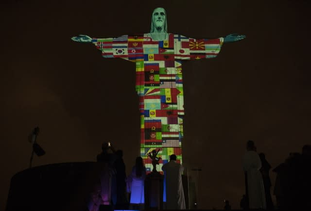 Rio's Christ the Redeemer statue is lit up with the flags of countries currently afflicted by the coronavirus (Silvia Izquierdo/AP)