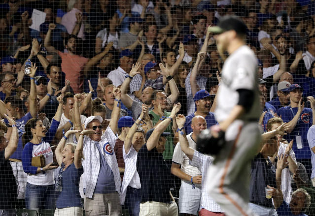 Chicago Cubs fans celebrate after Javier Baez hit a three-run home run during the fourth inning of a baseball game against the San Francisco Giants in Chicago, Sunday, May 27, 2018. (AP Photo/Nam Y. Huh)