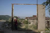 """Anahit Aleqyan stands next to the new Armenian-Azerbaijani border in Shurnkh village, about 200 km. (125 miles) south-east of Yerevan, Armenia, Tuesday, June 15, 2021. Shurnukh village, about 200 km. (125 miles) south east of Yerevan, Armenia, Tuesday, June 15, 2021. Anahit Aleqyan, a 65-year-old from the village of Shurnkh in southern Armenia, says that her village was cut in two by a newly defined border with Azerbaijan, and she lost her house in the peace deal. """"Every day I come here to gather thyme, look at (my house) and cry,"""" she lamented. (AP Photo/Areg Balayan)"""