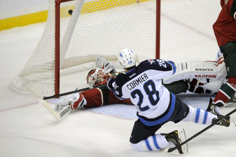 Winnigeg Jets' Patrice Cormier (28) hits the puck into the net over fallen Minnesota Wild goalie Niklas Backstrom in the second period of an NHL hockey game on Saturday, Sept. 21, 2013, in St. Paul, Minn. (AP Photo/Tom Olmscheid)