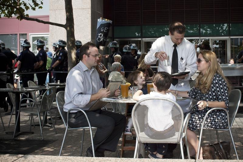 A family is served drinks at a restaurant while Occupy Wall Street activists protest through the streets of New York's Financial District on the one-year anniversary of the movement, in New York