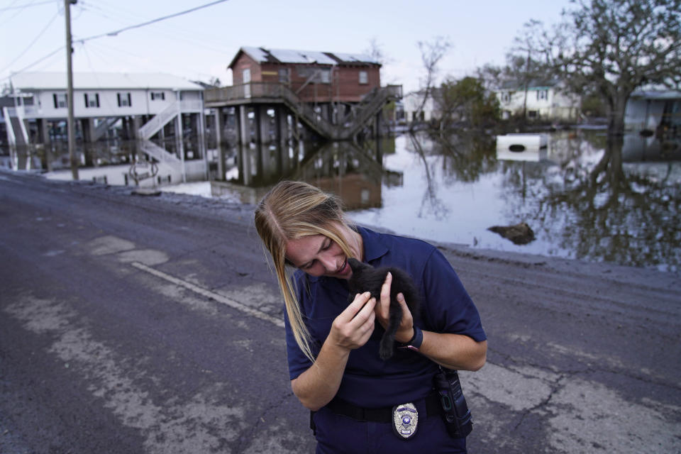 Lafayette Parish Deputy Rebecca Bobzin cradles a cat she helped rescue from a house surrounded by floodwaters in the aftermath of Hurricane Ida, Sunday, Sept. 5, 2021, in Lafitte, La. (AP Photo/John Locher)