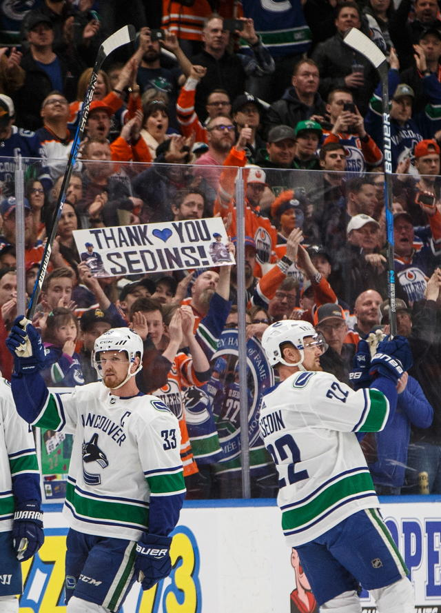Vancouver Canucks' Henrik Sedin (33) and Daniel Sedin (22) acknowledge the crowd as they cheer for them during a break against the Edmonton Oilers in Edmonton, Alberta, Saturday, April 7, 2018. (Jason Franson/The Canadian Press via AP)