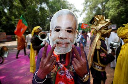 A supporter of India's Bharatiya Janata Party (BJP) celebrates after learning of the initial poll results outside the party headquarters in New Delhi