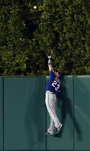 Texas Rangers center fielder Craig Gentry can't catch a two-run home run ball off Los Angeles Angels Howie Kendrick in the fourth inning of a baseball game in Anaheim, Calif., on Tuesday, April 23, 2013. (AP Photo/Christine Cotter)