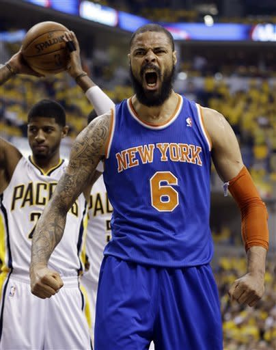 New York Knicks' Tyson Chandler (6) reacts in front of Indiana Pacers' Paul George after making a basket and being fouled during the first half of Game 3 of an Eastern Conference semifinal NBA basketball playoff series in Saturday, May 11, 2013, in Indianapolis. (AP Photo/Darron Cummings)
