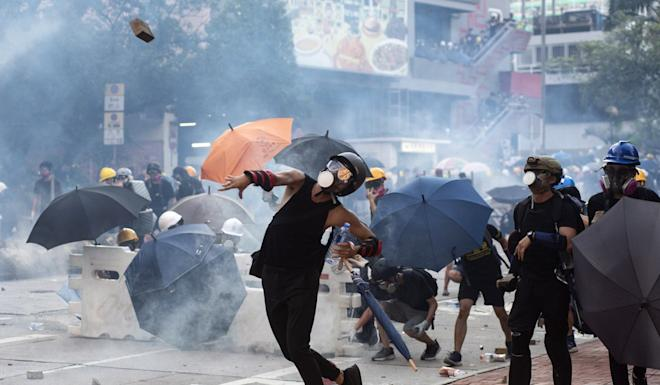 Protesters throw bricks after police fired tear gas during clashes in Wong Tai Sin on August 5. Photo: EPA