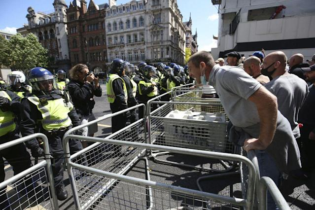 Police clash with far-right demonstrators during their protest to 'guard' statues in London. (PA)