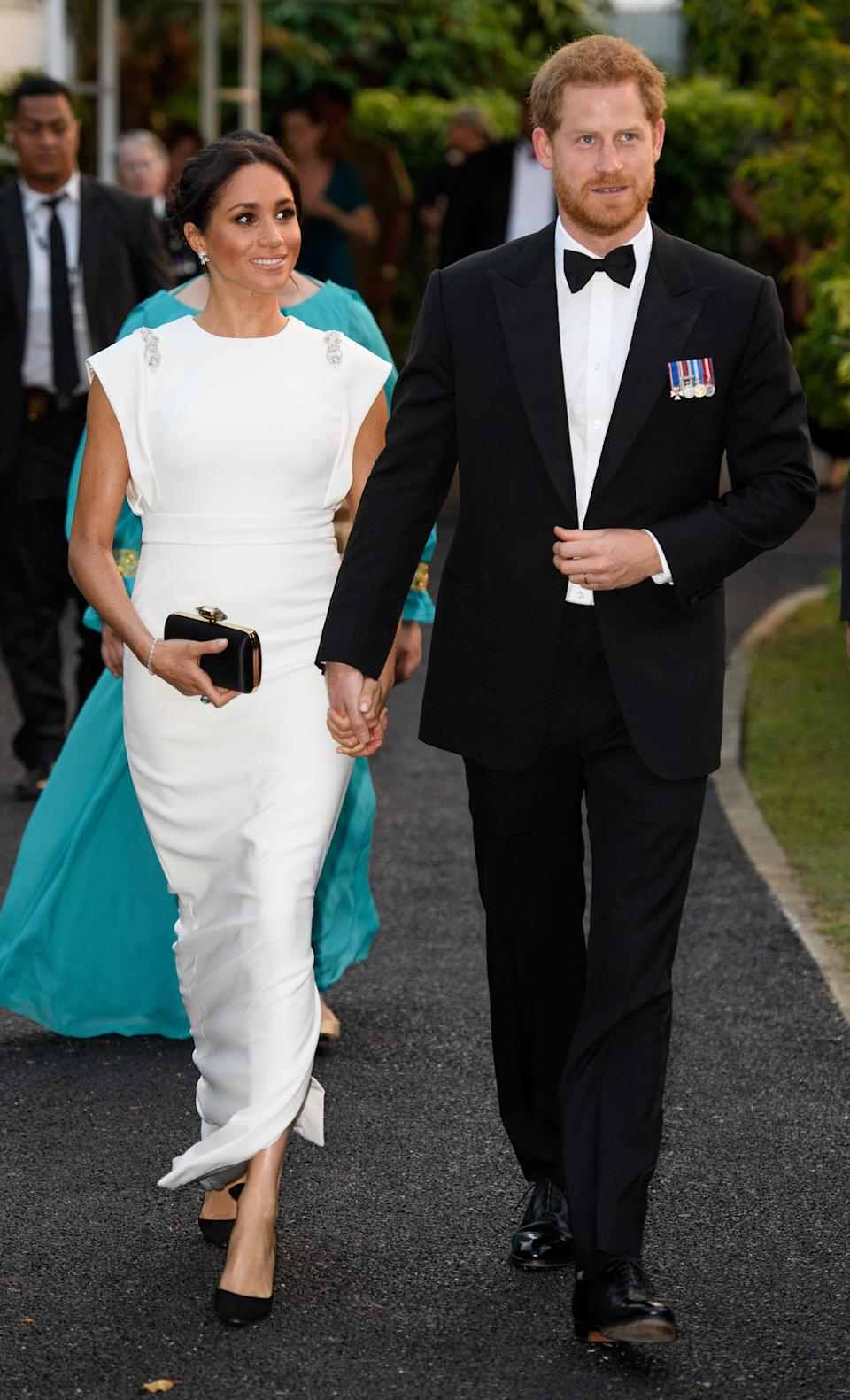 <p>For an evening reception and dinner in Tonga, the Duchess wore a white gown by Theia Couture with Aquazzura shoes, Birks earrings and her go-to Givenchy clutch. In a touching nod to Princess Diana, the Duchess finished the look with the late royal's aquamarine ring. <em>[Photo: Getty]</em> </p>