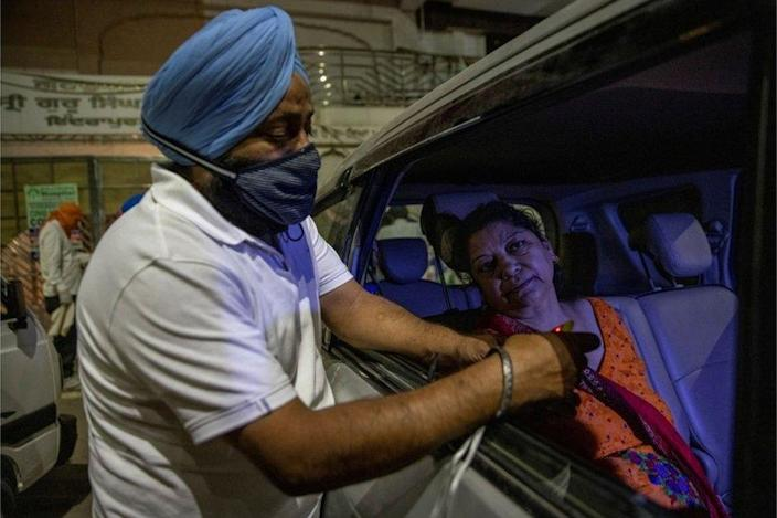 A volunteer uses an oximeter to check the oxygen level of a woman before providing oxygen support for free, amidst the spread of coronavirus disease (COVID-19), outside a Gurudwara (Sikh temple) in Ghaziabad, India, April 24, 2021