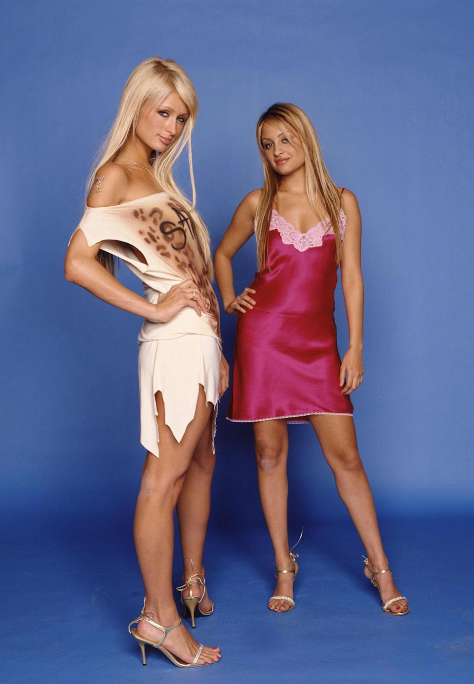 <p>We love that Nicole's pink silk slip dress and Paris's cutout graffiti number are both styled with strappy heels.</p>