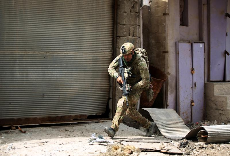 An Iraqi soldier runs for cover as government forces battle Islamic State group jihadists for control of Mosul's Old City