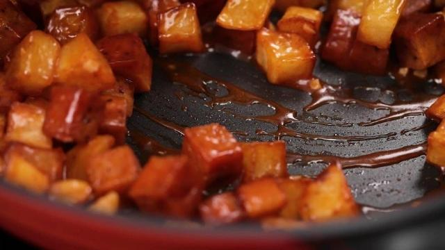 stir frying potatoes and luncheon meat in sauce in a pan
