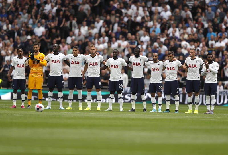 Tottenham players observe a minute of silence in memory of former player and manager Justin Edinburgh prior to the start of the English Premier League soccer match between Tottenham Hotspur and Aston Villa at the Tottenham Hotspur stadium in London, Saturday, Aug. 10, 2019. (AP Photo/Frank Augstein)