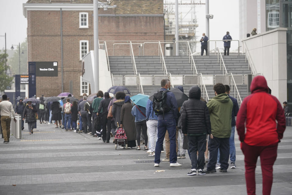 People queue at an NHS Vaccination Clinic at Tottenham Hotspur's stadium in north London, Sunday, June 20, 2021. The NHS is braced for high demand as anyone in England over the age of 18 can now book a Covid-19 vaccination jab. (Yui Mok/PA via AP)