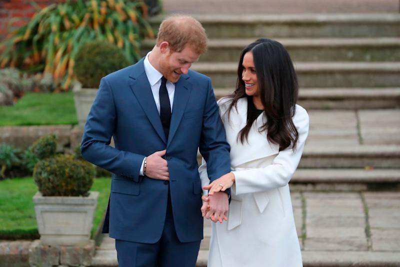 Prince Harry and fiancée Meghan Markle stroll blissfully around Kensington Palace's Sunken Garden for their official engagement photos. (Photo: Getty Images)