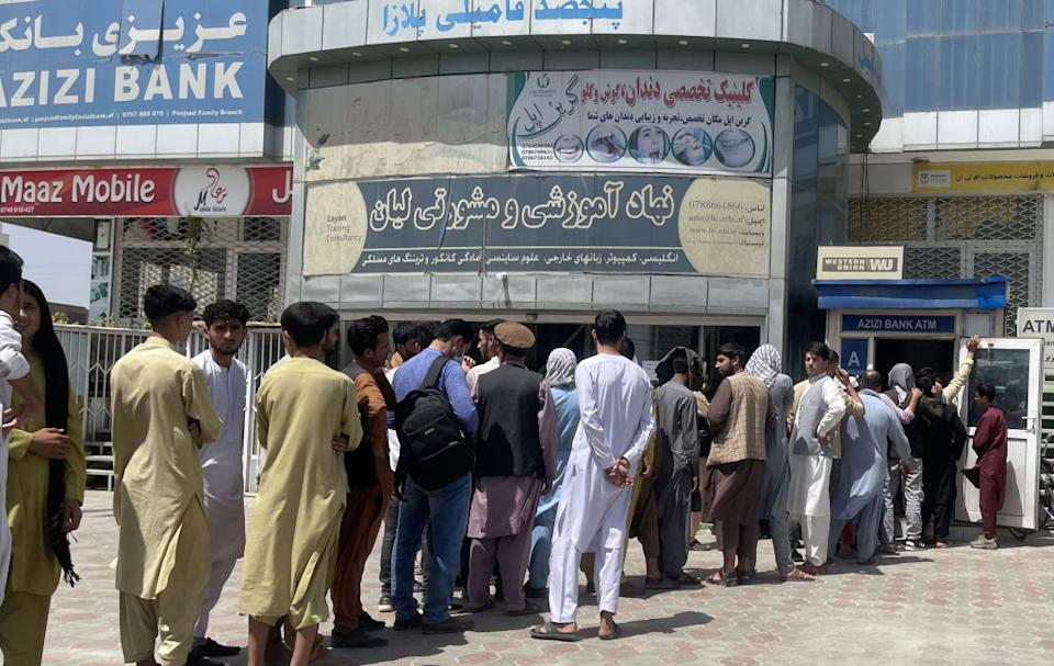 Afghan people line up outside AZIZI Bank to take out cash as the Bank suffers amid money crises in Kabul, Afghanistan.
