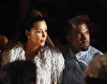 West drapes his arm over the shoulder of Kardashian as they watch a showing of the Marchesa Spring/Summer 2013 collection during New York Fashion Week