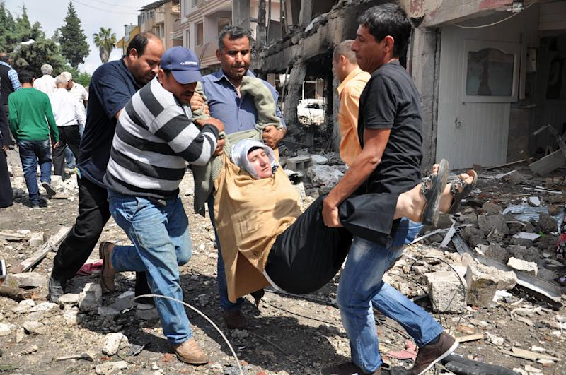 People carry a woman injured in a blast in Reyhanli, near Turkey's border with Syria, Saturday, May 11, 2013. Two car bombs exploded in a Turkish town near the border with Syria on Saturday, killing and injuring scores of people officials and media reports said. (AP Photo/Anadolu Agency, Lale Koklu) TURKEY OUT