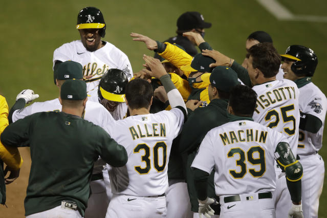 Oakland Athletics players celebrate after Matt Olson, center left, hit a grand slam home run against the Los Angeles Angels in the tenth inning a baseball game in Oakland, Calif., Friday, July 24, 2020. (AP Photo/Jeff Chiu)