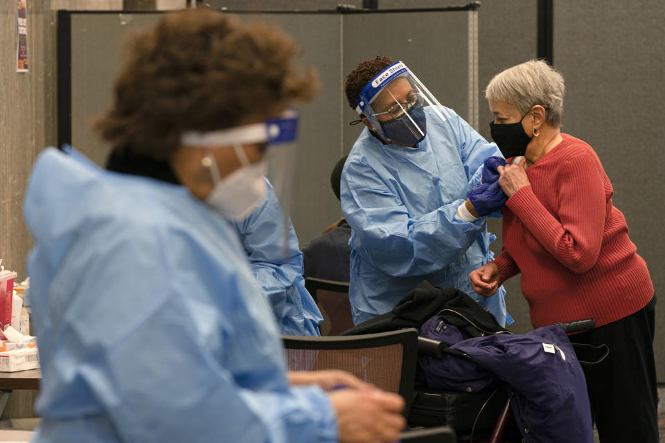 """In this Thursday, Feb. 11, 2021, photo Charlotte Lee, 78, of Washington, right, prepares to receive her second dose of the COVID-19 vaccine at a clinic at Howard University, in Washington. """"I have underlying conditions so I had no hesitation in getting this vaccine,"""" says Lee, who signed up at Howard after being unsuccessful at using the city's vaccination sign-up site. (AP Photo/Jacquelyn Martin)"""