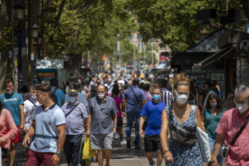 People walk along the Ramblas of Barcelona, Spain, Thursday, July 16, 2020. With Europe's summer vacation season kicking into high gear for millions weary of months of lockdown, scenes of drunken British and German tourists on Spain's Mallorca island ignoring social distancing rules and reports of American visitors flouting quarantine measures in Ireland are raising fears of a resurgence of infections in countries that have battled for months to flatten the COVID-19 curve. (AP Photo/Emilio Morenatti)