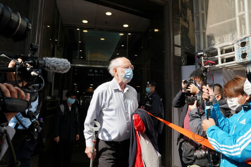 American lawyer John Clancey walks out of a building as he is taken away by police officers in Hong Kong