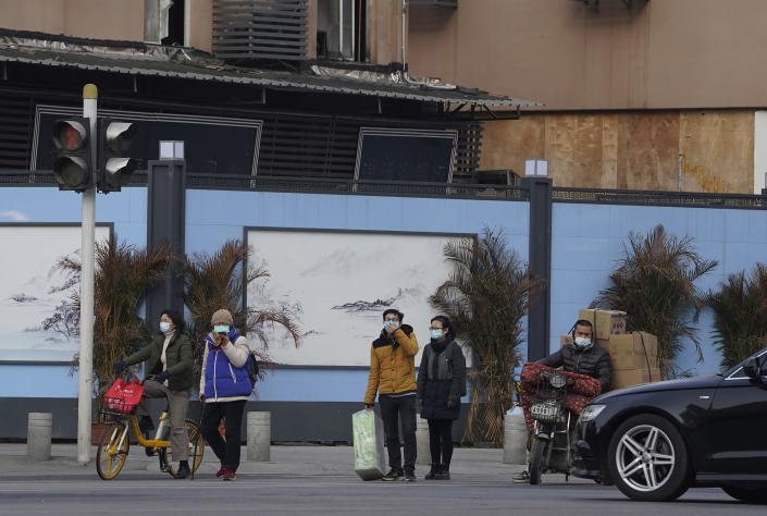 Residents wearing masks to protect from the coronavirus pass by the shutdown Huanan Seafood Market in Wuhan in central China's Hubei province on Friday, Jan. 15, 2021. Scientists initially suspected the coronavirus came from wild animals sold in the market. The market has since been largely ruled out but for the visiting WHO team of international researchers it could still provide hints to how the virus spread so widely. (AP Photo/Ng Han Guan)